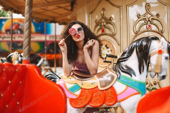 Pretty girl in sunglasses covering her eye with lolly pop candy at carousel horse in amusement park
