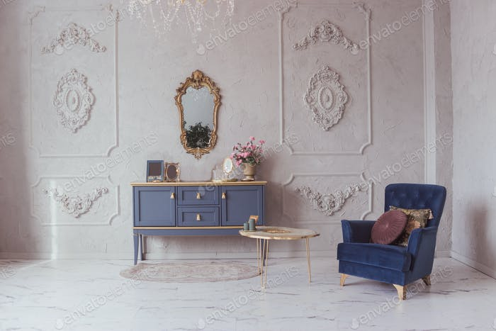 Luxurious interior with a chest of drawers and velvet armchair in a classic style