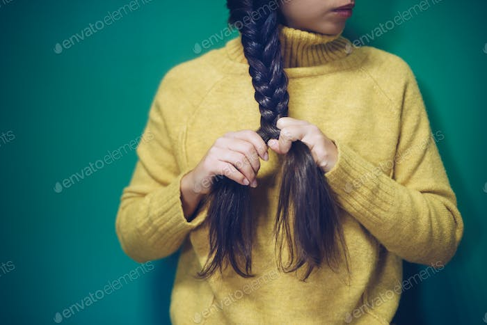 Girl is plaiting her hair