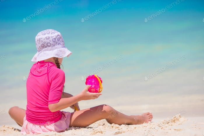 Adorable happy little girl at shallow water with beach toys