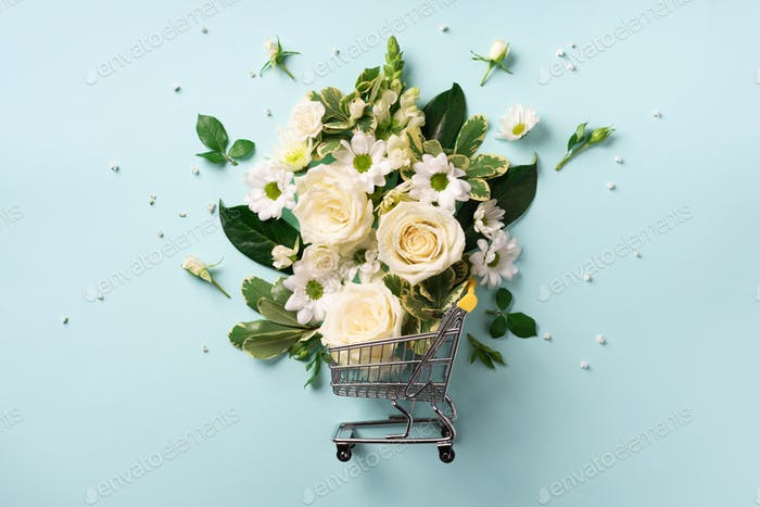 Shopping trolley with flowers on blue pastel background. Banner with copy space. Top view, flat lay
