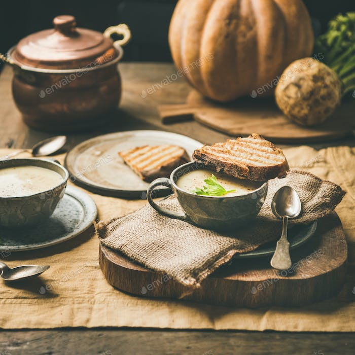 Celery cream soup, toast, fresh pumpkin at background, square crop