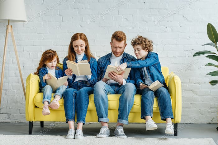 Parents and children sitting on sofa and reading books