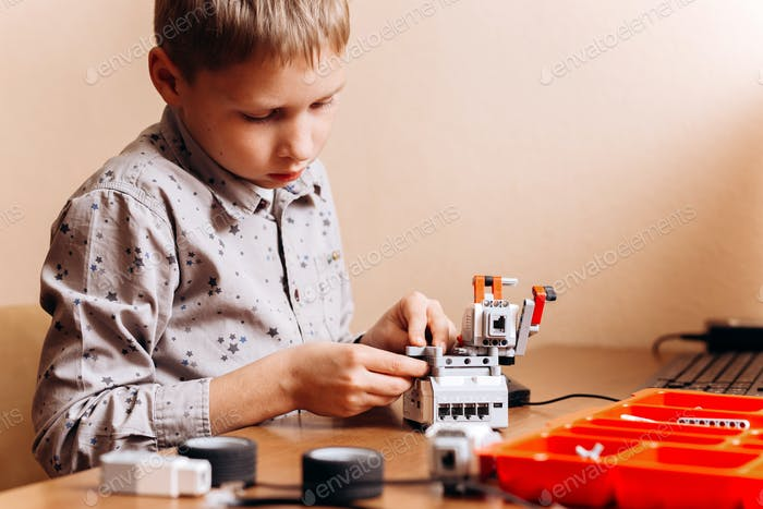 Boy dressed in gray shirt makes a robot from the robotic constructor at the desk in the School of