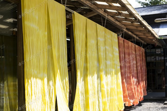 Freshly dyed bright yellow and orange fabric hanging outside a textile plant dye workshop.