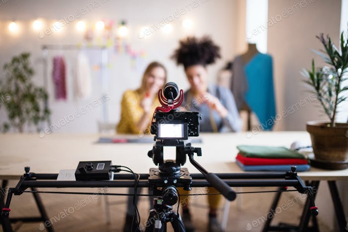 A camera and a slider with women in the background, startup business.
