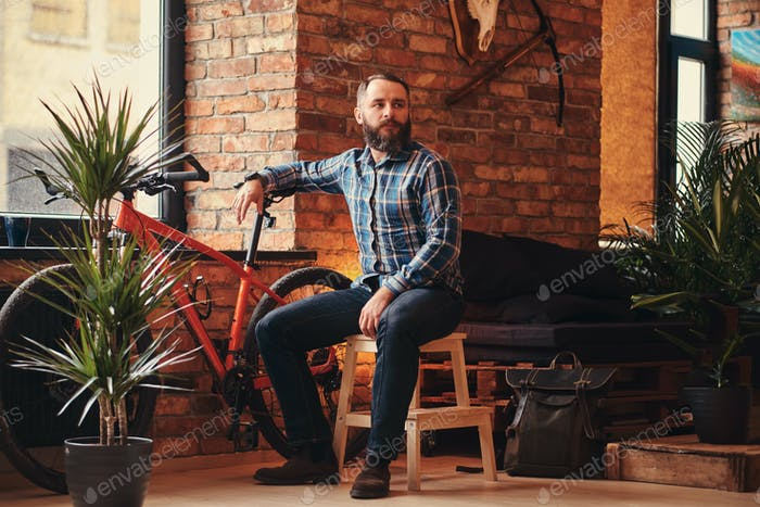Handsome bearded hipster male sitting on a wooden stool at a studio with loft interior.