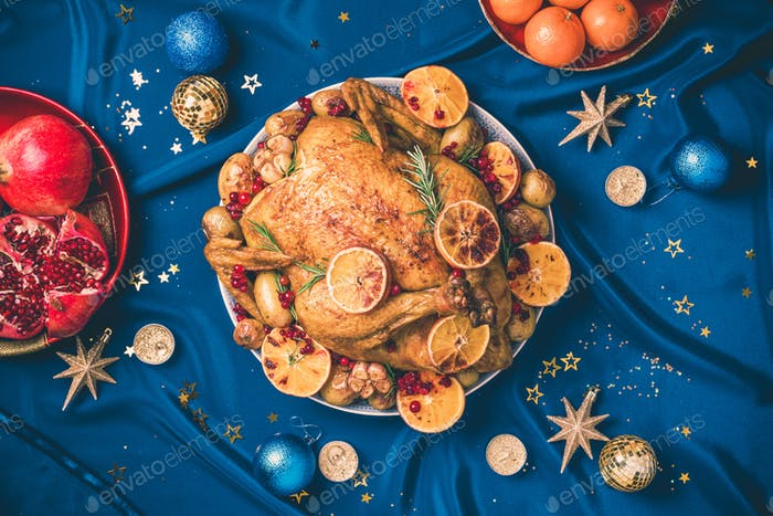 Roasted Christmas turkey with orange slices, cranberries, garlic, festive decoration, candles