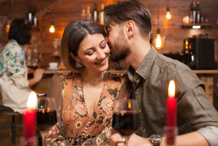 Young man kissing his fiance on a night out