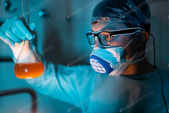 Young male researcher carrying out scientific experiment