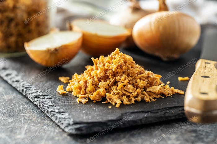 Pieces of fried onions on cutting board.