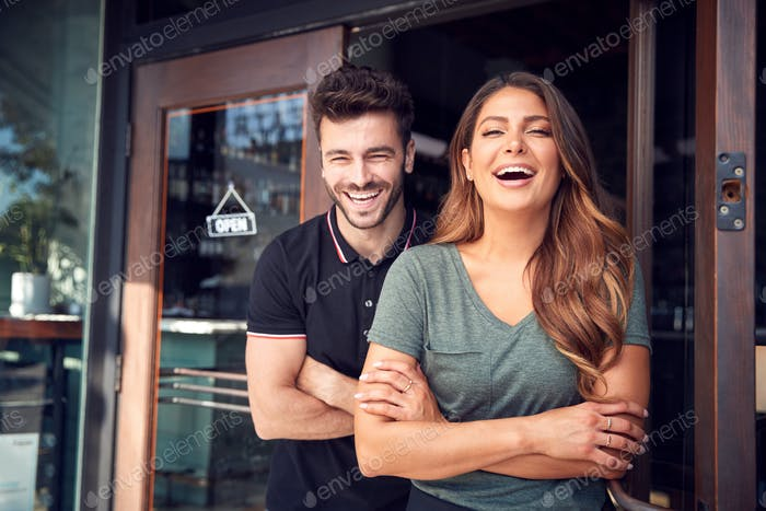 Portrait Of Couple Starting New Coffee Shop Or Restaurant Business Standing In Doorway