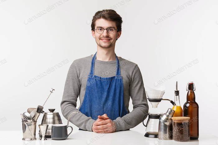 Barista, cafe worker and bartender concept. Friendly-looking happy smiling young male employee ready