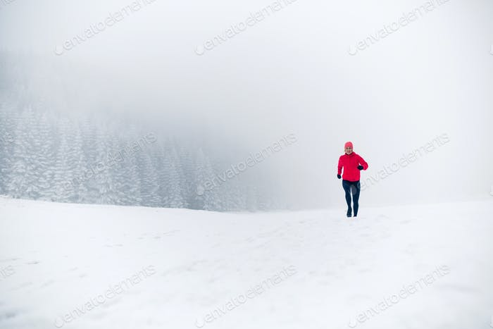 Woman running on snow in winter mountains