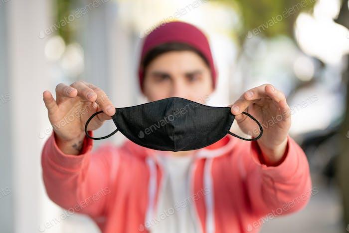 Junger Mann trägt Gesichtsmaske im Freien.