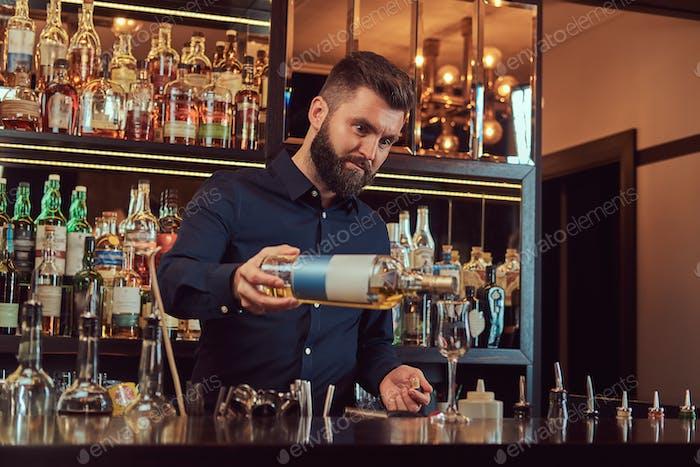 Barkeeper in einem schwarzen Hemd präsentiert eine Flasche exklusiven Alkohol am Bartheke Hintergrund.