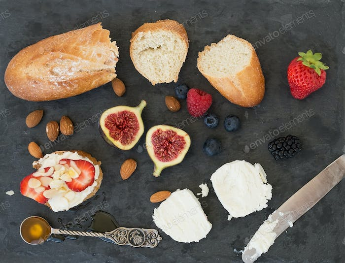 Bread, goat cheese, almond, honey and berries on a dark surface