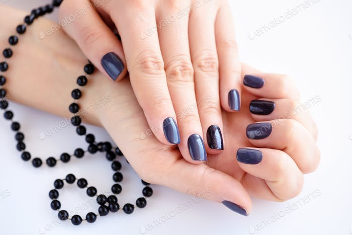 Beautiful hands of a young woman with dark manicure holding blac