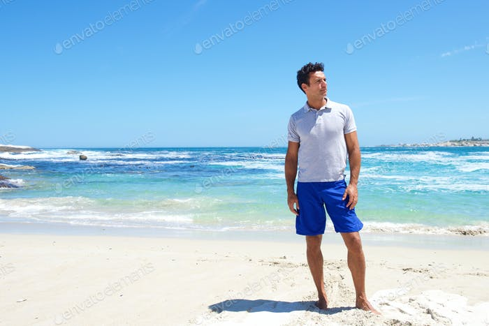 Fit middle aged man standing barefoot at the beach