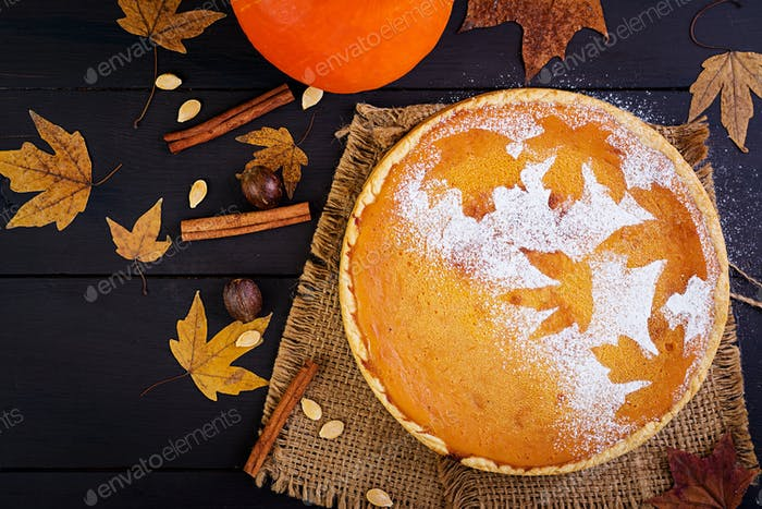 American homemade pumpkin pie with cinnamon and nutmeg, pumpkin seeds and autumn leaves