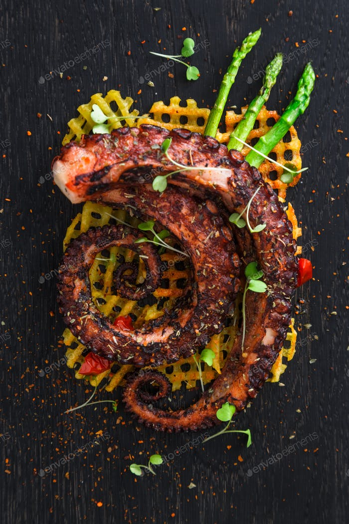 Close up octopus tentacles withpotatoes and lemon on black plate