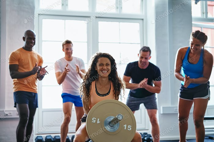 Smiling woman lifting weights with friends cheering in the background