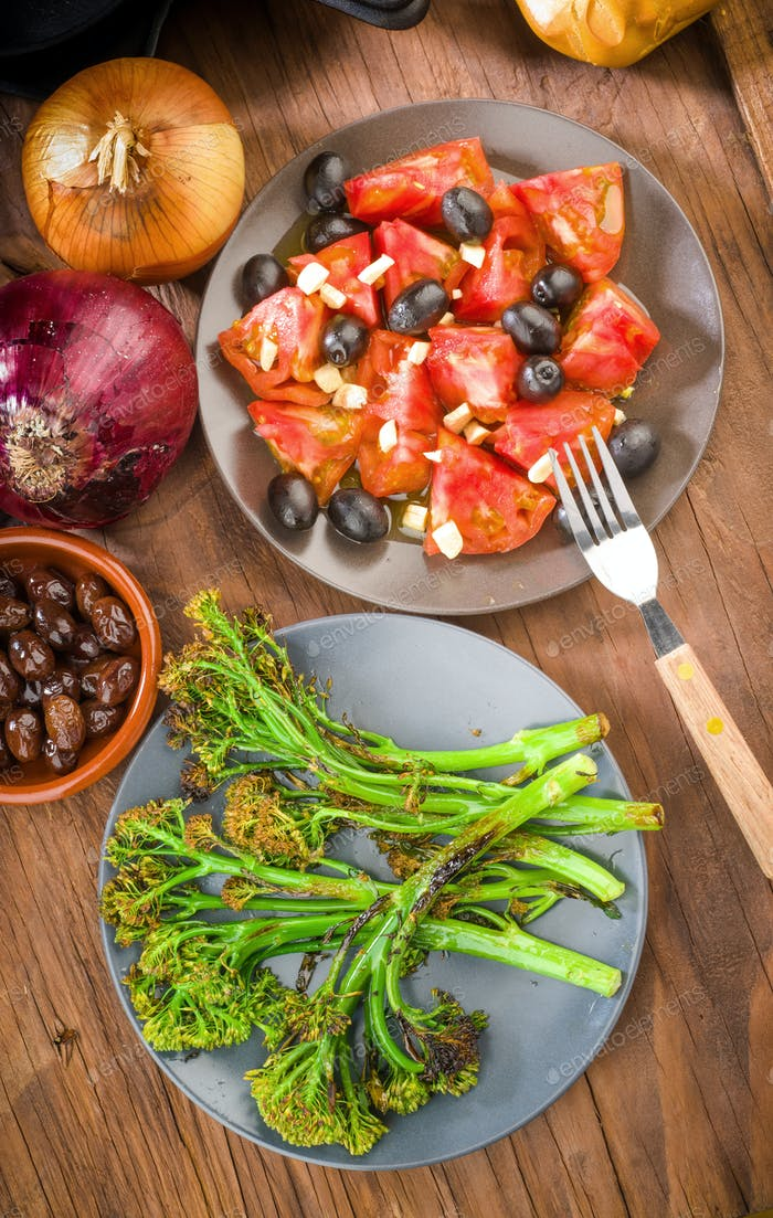 dish with tender shoots of broccoli and grilled tomato salad