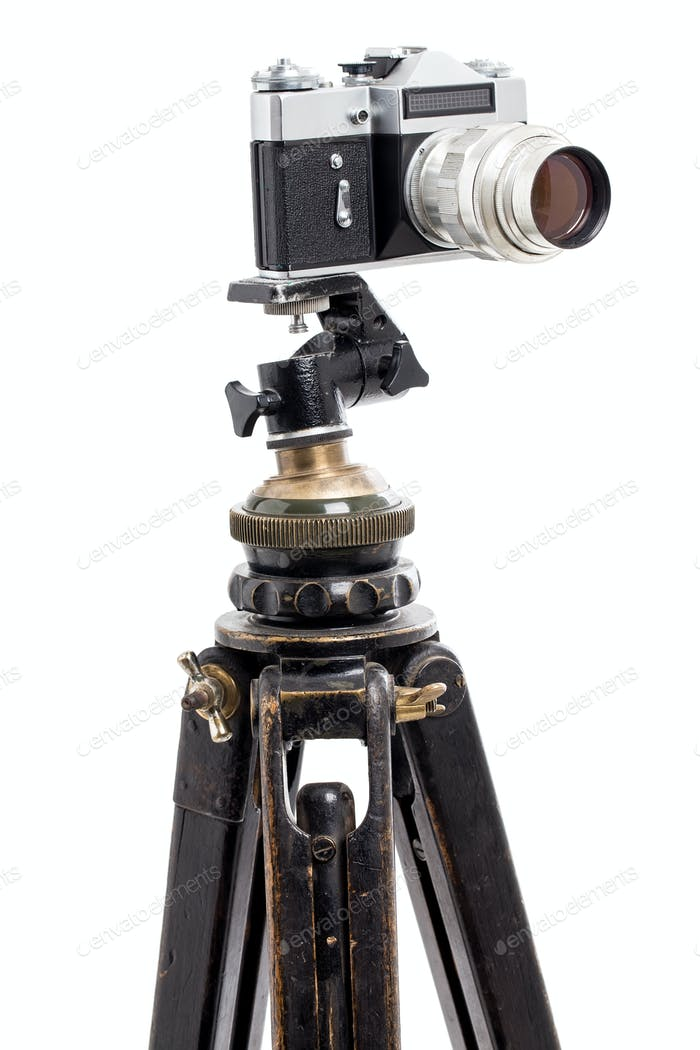 Old film photocamera on wooden tripod.