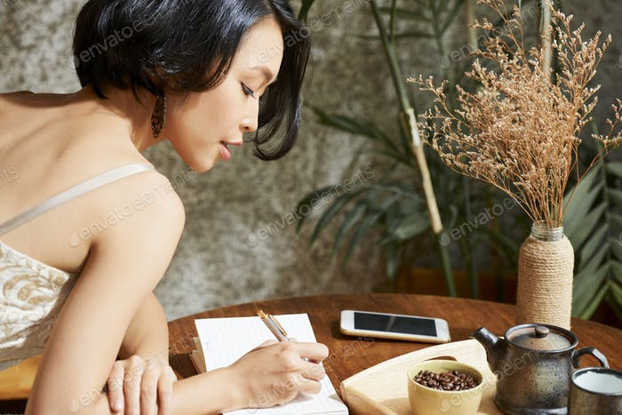 Woman filling gratitude journal