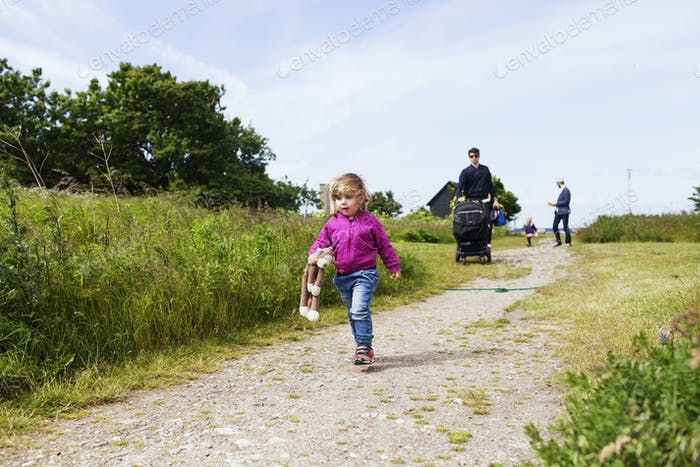 Family and friends walking amidst grassy field