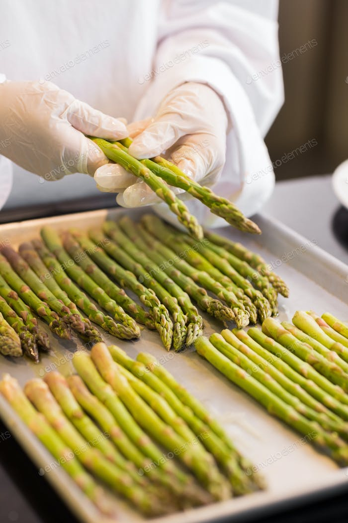 Closeup of hands with fresh asparagus in the kitchen