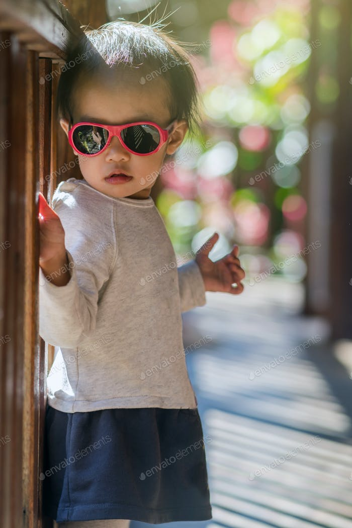 Portrait of Asian girl wear glasses at home or resort, Children and family concept