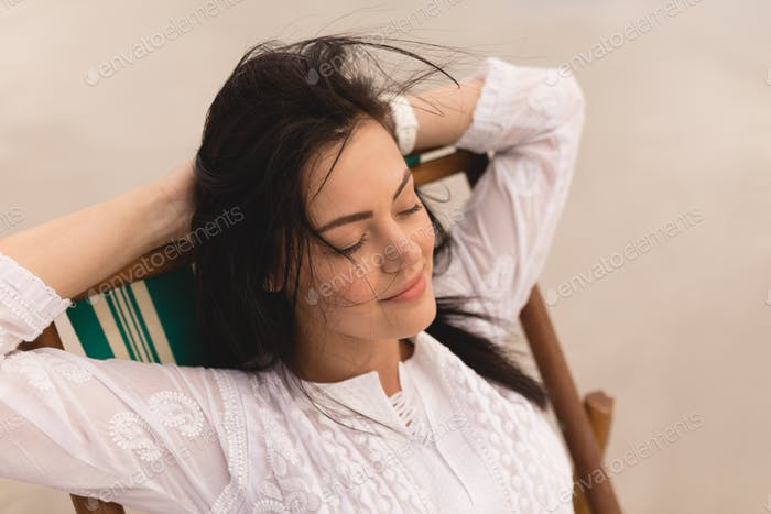 Front view of young woman with eyes closed and hands behind head relaxing on sun lounger at beach