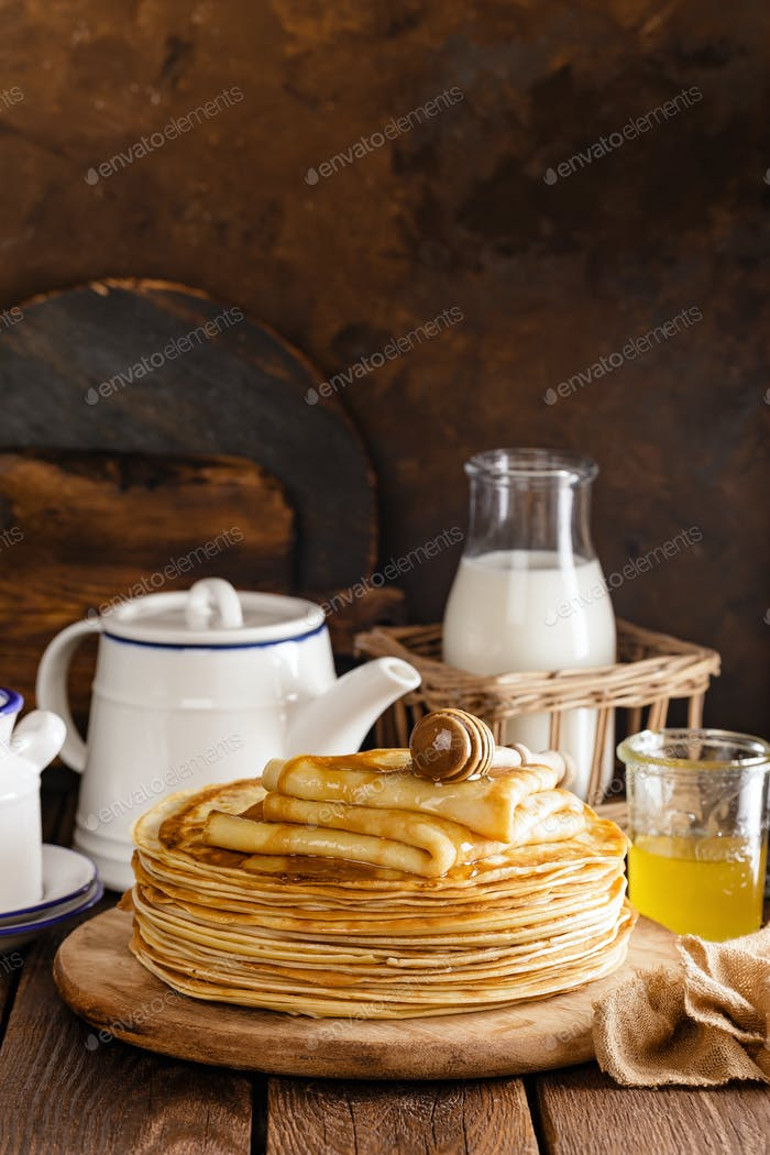 Homemade thin crepes with honey, pancakes on wooden rustic background