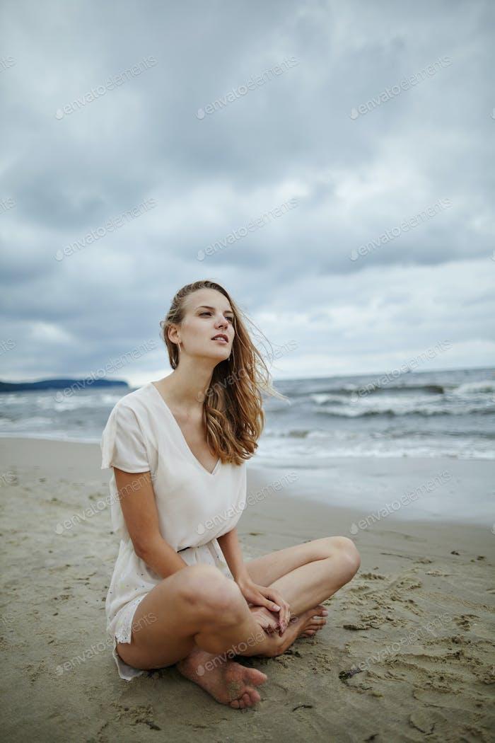 junge schöne Frau am kalten windigen Strand