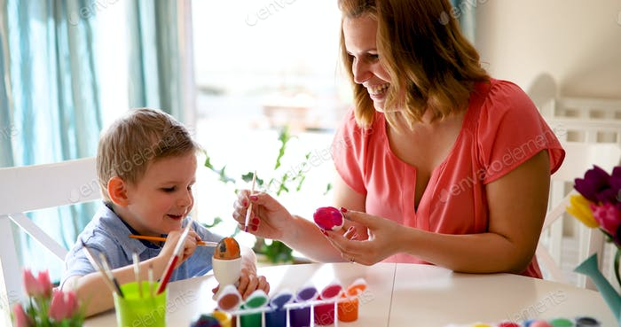 Mother and son are painting eggs