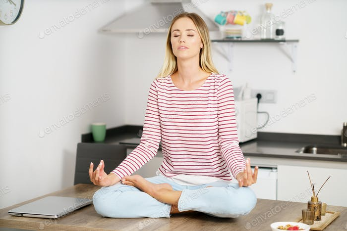 Young blonde woman meditating in the kitchen at home