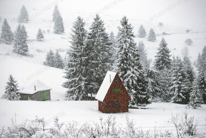 Cabaña cubierta de nieve en las montañas