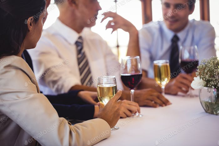 Business people talking with each other at the table in restaurant
