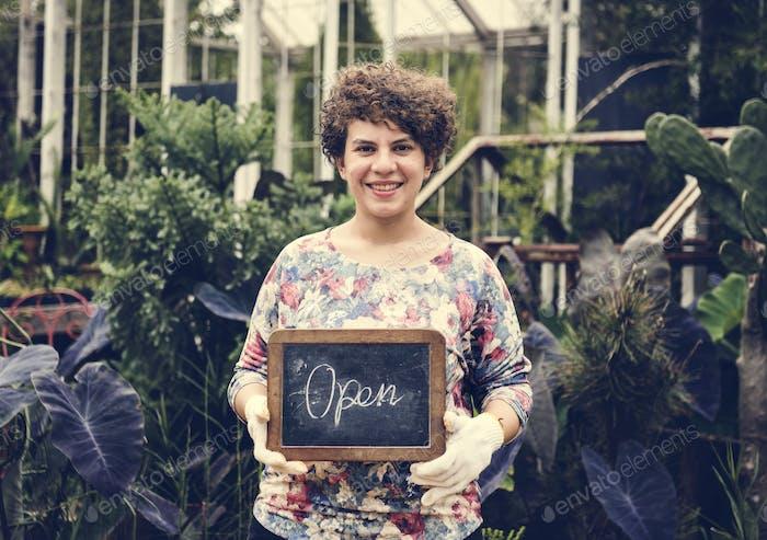 Gartenladen Besitzer hält ein offenes Schild