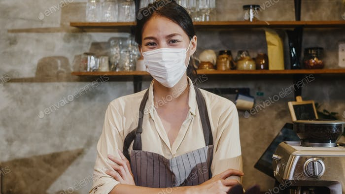 Portrait young Asia girl waitress wear medical face mask feeling happy smile waiting for clients.