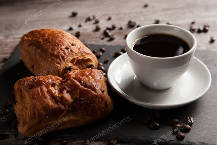 Mug of coffee with delicious pastry and spreaded beans of coffee