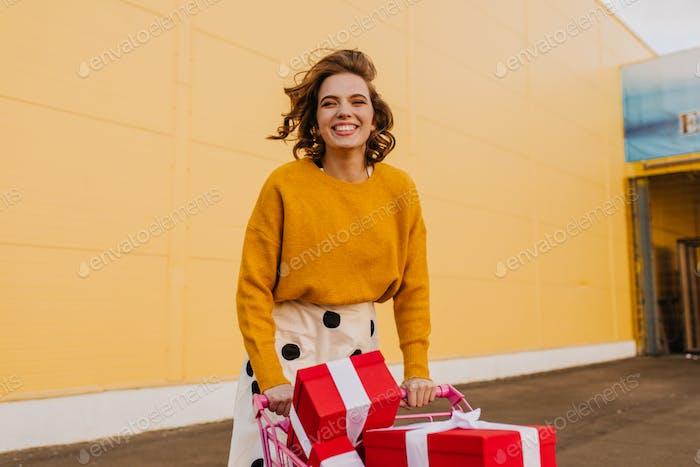 Mujer joven inspirada posando con carrito de la compra y riendo. Bastante pelo corto dama comprando presen
