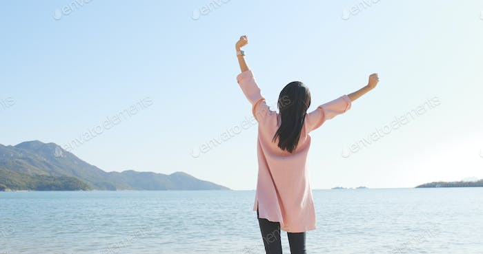 Excited woman raining up and standing at the beach