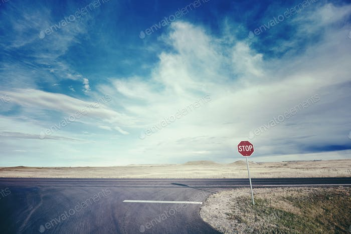 Retro stylized picture of a highway with a stop sign, USA