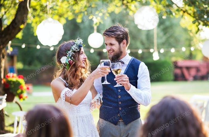 Braut und Bräutigam mit Gästen am Hochzeitsempfang draußen im Hinterhof.