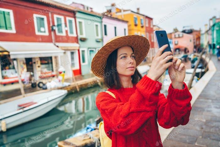Beautiful tourist takes photos outdoors