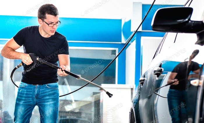Professional carwash employee washing car at wash station