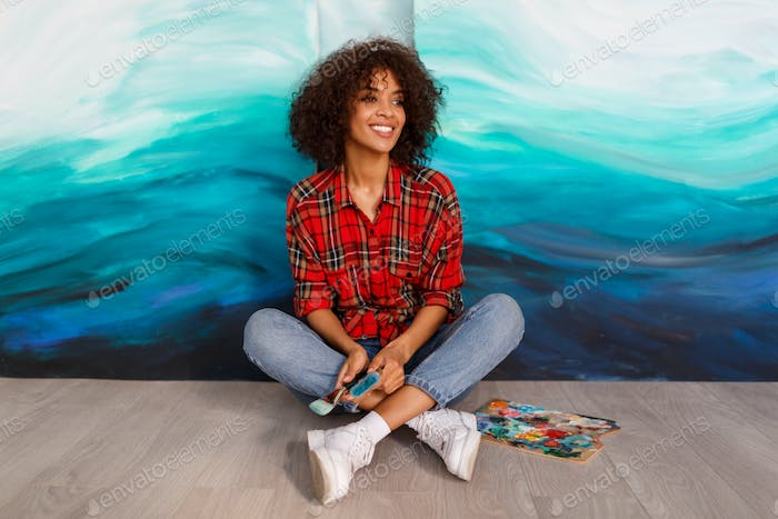 Beautiful  cute african ethnicity student  holding brushes and posing over her abstract artworks