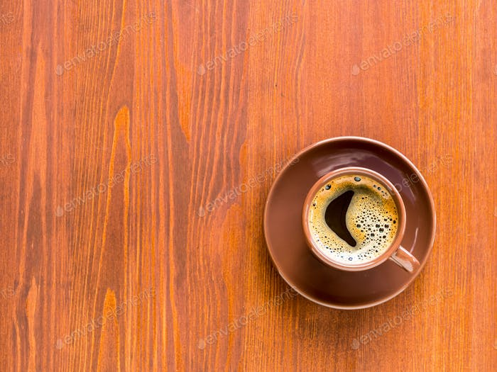 Brown cup of frothy coffee on wooden background.